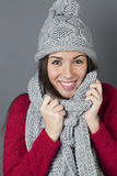 Thrilled female teenager wrapping herself in soft winter scarf Stock Image