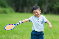 Thrilled Little kid play with tennis. Asian young little boy at outdoor royalty free stock images