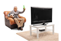 Thrilled mature man watching football on TV. Thrilled mature man sitting on an armchair having a beer and watching football on TV isolated on white background royalty free stock photos