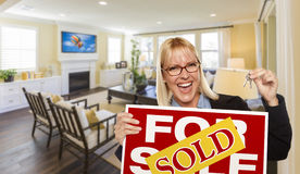 Thrilled Realtor Holding Sold Sign and Keys Inside Living Room. Happy Young Woman Holding Sold For Sale Real Estate Sign and Keys Inside Beautiful Custom Living Royalty Free Stock Image