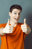 Thrilled 20s athletic man and thumbs up for ok or success Stock Images