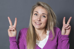 Thrilled 20s woman showing two victory signs Stock Photos