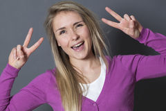 Thrilled 20s woman showing 2 victory signs Royalty Free Stock Image