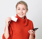 Thrilled young blond woman making a shopping transaction online Royalty Free Stock Image