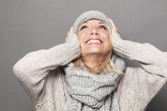 Thrilled young blonde woman smiling for warmth and cozyness in winter Stock Photos
