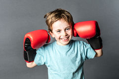 Thrilled young boy giggling with boxing gloves up for fight. Thrilled young 6-year old boy with red hair giggling and holding his big boxing gloves up for a Stock Images