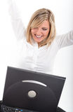 Thrilled young woman with laptop. Portrait of an ecstatic young blonde throwing her arms in a victory gesture Royalty Free Stock Photo