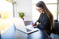 Thrilled young woman manager taking notes on good news on headset and notebook in office. Thrilled young female manager taking notes on good news on headset and Stock Image