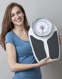 Thrilled young woman proud of displaying her kilos or pounds loss. Weight and diet control concept - focused young woman smiling with weighting scale in hands stock photo