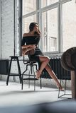 Thrilling memories. Attractive young woman in elegant black dres. S looking through the window while sitting on the chair at home Stock Photo