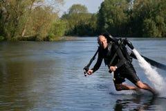 Thrillseeker,水上运动恋人,运动员被束缚喷射列弗,升空盘旋在有蓝天和树的湖 库存照片
