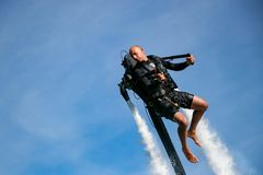 Thrillseeker, athlete strapped to Jet Lev, levitation soars into a blue sky with whispy clouds Stock Photo