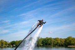 Thrillseeker, atleta attaccato a Jet Lev, levitazione sale in un cielo blu con le nuvole whispy immagine stock