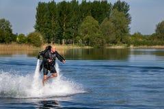 Thrillseeker, sport acquatici amante, atleta attaccato a Jet Lev, levitazione sorvola il lago con cielo blu e gli alberi fotografie stock libere da diritti