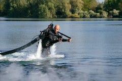 Thrillseeker, sport acquatici amante, atleta attaccato a Jet Lev, levitazione sorvola il lago con cielo blu e gli alberi immagini stock