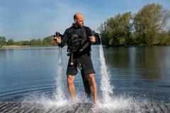 Thrillseeker, sport acquatici amante, atleta attaccato a Jet Lev, levitazione sorvola il lago con cielo blu e gli alberi fotografia stock