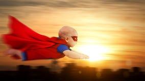 有红色海角飞行thro的小孩小小超人超级英雄 免版税库存照片