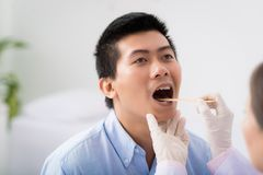 Throat examination. Doctor examining throat of patient with tongue depressor Royalty Free Stock Images