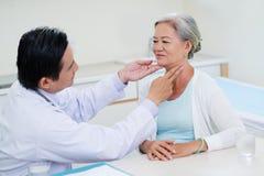 Throat examination. Doctor examining throat of senior women during regual check-up stock image