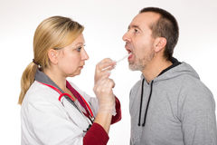 Throat examining. A doctor is looking into a patients throat Stock Photos