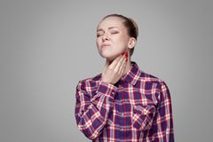 Throat pain. sick blonde girl in red, pink checkered shirt, collected bun hairstyle, makeup standing and touching her painful neck. Indoor studio shot stock image