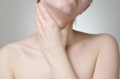 Throat pain. Young woman holding her painful throat Royalty Free Stock Photos
