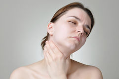 Throat pain. Young woman holding her painful throat Stock Photos