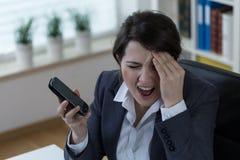 Throbbing headache. Young stressed businesswoman with throbbing headache Stock Photography