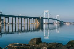 Throgs Neck Bridge with clear reflection in water. And rocks in foreground viewed from Little Bay park on a sunny day in Beechhurst, Queens, NY stock photography