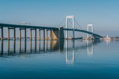 Throgs Neck Bridge with clear reflection in water. Viewed from Little Bay park on a sunny day in Beechhurst, Queens, NY royalty free stock images