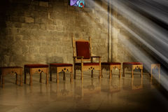 Throne. With antique wooden chairs in a dark room with an old stone wall in the background and the rays of sunlight falling from a window, a symbol of power and royalty free stock photos