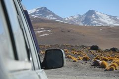 A car in a bolivian desert. Throughout the year, 4x4 cars cross Eduardo Evaroa National Park taking thousands of tourists through the Andean mountains Royalty Free Stock Image