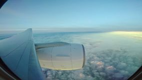 Throught plane window view of jet plane flying over cloud scape