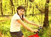 Throuth adolescente de la bicicleta del paseo de la muchacha el bosque Fotos de archivo libres de regalías