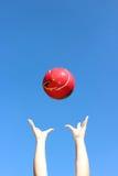 Красное throuwn шарика в воздухе стоковое изображение rf