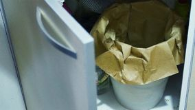 Throw away trash. Woman throwing away trash in the kitchen trash bin stock footage