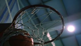 Throw a ball into the basketball ring against the backdrop of searchlights. Slow motion. Throwing a basketball ring against the blue spotlights, the ball hits stock footage
