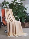 Throw draped over a chair. Throw draped over a modern chair stock photos