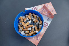 Throw money into the ashtray Royalty Free Stock Photo