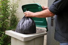 Throw a plastic bag in the trash. Unrecognizable man throwing a plastic bag in the trash in close-up stock photography