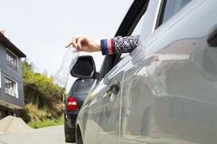 Throw plastic bottle from the car. Hand of a woman royalty free stock photo