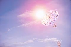 Throw umbrella. Hand throw umbrella up to blue sky stock photo
