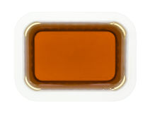 Throwaway container of maple syrup. Top view of a plastic throwaway container filled with maple syrup on a white background Stock Image