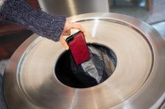 Throwing away mobile phone into rubbish bin. Female hand throwing away mobile phone into rubbish bin stock photos