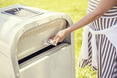 Throwing away trash in an outdoor trash can Royalty Free Stock Image