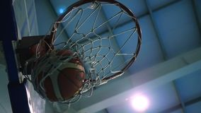 Throw a ball into the basketball ring against the backdrop of searchlights. Slow motion. Throwing a basketball ring against the blue spotlights, the ball hits stock video