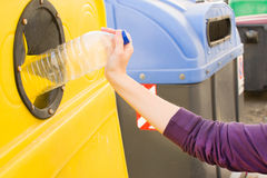 Throwing a bottle into the recycling container Stock Image