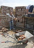 Throwing bricks wheelbarrow Royalty Free Stock Images