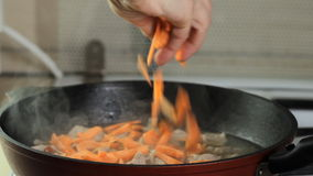Throwing carrots into a frying pan stock video