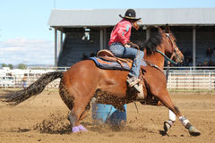 Throwing Dirt - Barrel Racer at Rodeo. Barrel racing cowgirl going around the barrels Stock Image